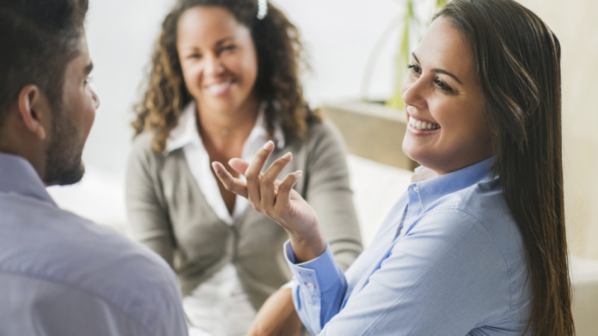 Young smiling businesswoman communicating with her colleagues in the office.