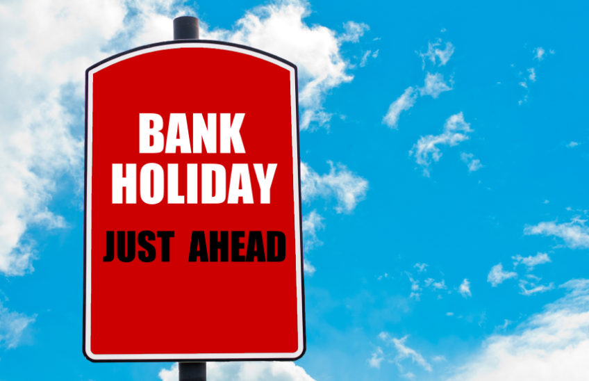 Bank Holiday Just Ahead motivational quote written on red road sign isolated over clear blue sky background. Concept  image with available copy space